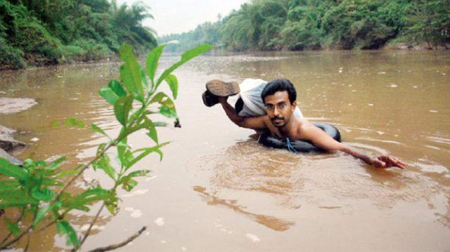 Chaque jour cet enseignant de Kerala traverse une rivière boueuse à la nage pour rejoindre son école