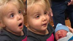 Une fille essaie d'embrasser son petit frère nouveau-né. Mais sa réaction - son visage en dit long