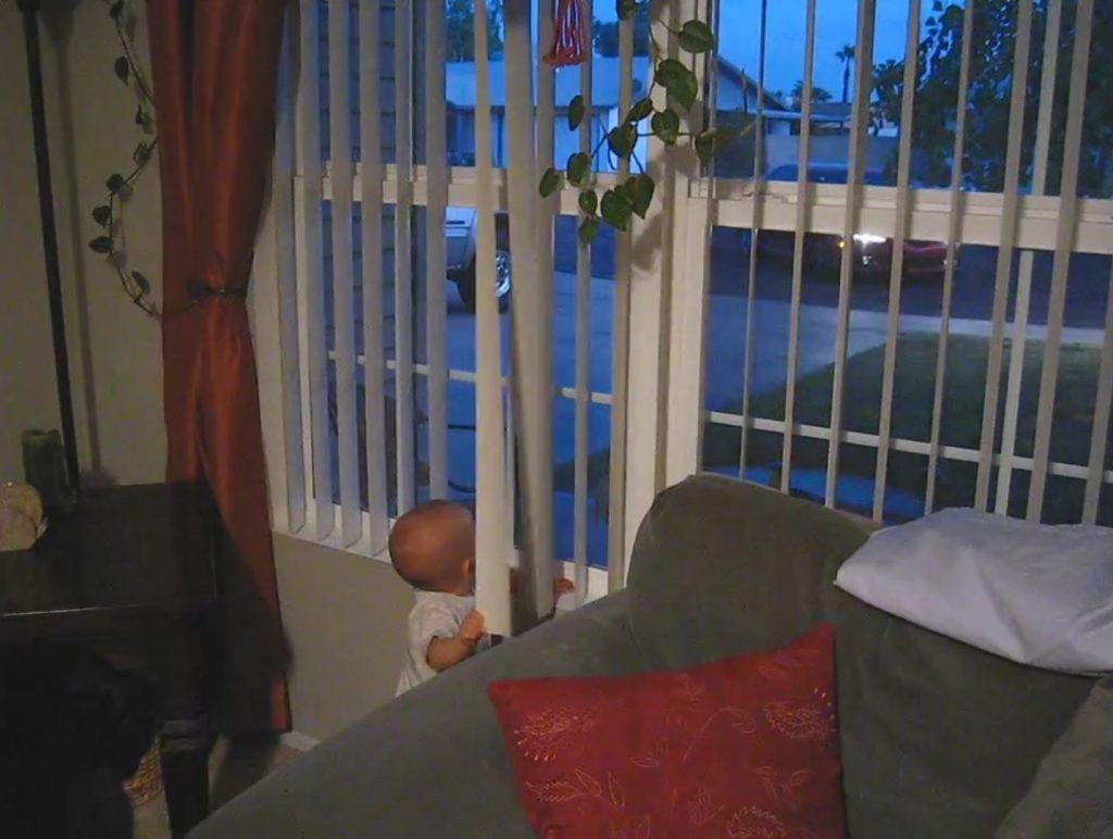 Un enfant d un an regarde par la fen tre lorsqu un homme for Assis a la fenetre