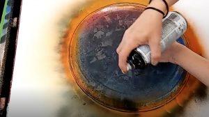 Une artiste peint au spray tout autour d'un couvercle métallique. Mais quand elle le soulève – j'ai le souffle coupé