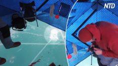 Des pêcheurs à la ligne applaudissent après avoir repéré une truite monstrueuse à travers la glace, ils réussissent à la faire passer à travers un trou de 20 cm