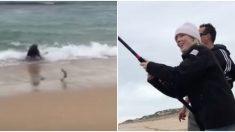 Une jeune femme à la plage capture un poisson. Mais quand elle enroule sa ligne, quelque chose d'autre sort de la mer pour le chasser
