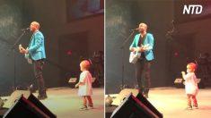 Un tout-petit prend d'assaut la scène pendant que papa chante. Il soulève l'enthousiasme quand il se met à danser joyeusement