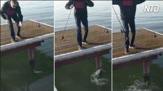 Un homme frappe l'eau frénétiquement avec une canne à pêche après la rupture de sa ligne. C'est son jour de chance quand il la remonte
