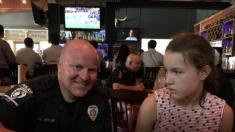 Maman essaie d'apprendre à sa fille que les policiers sont là pour l'aider lorsque l'agent le démontre en personne