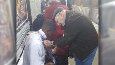À la gare ferroviaire, un homme âgé montre à un jeune homme comment nouer une cravate après l'avoir vu se démener